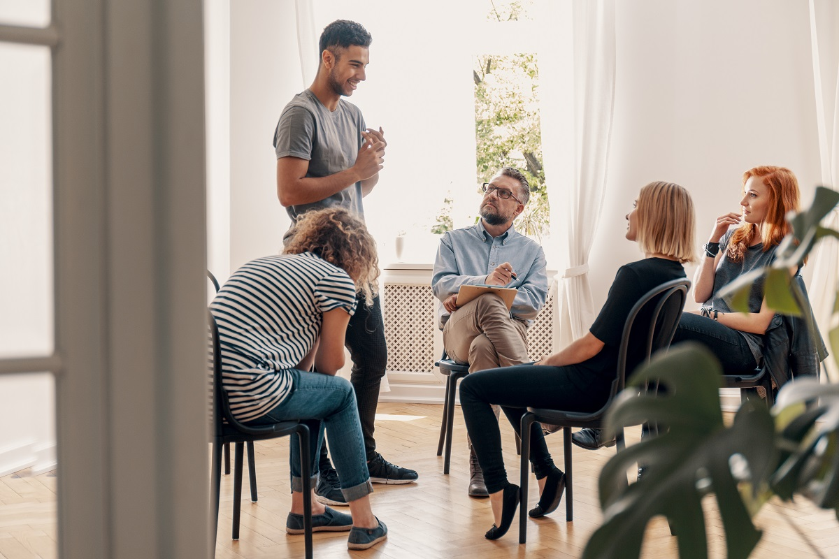 man talking to his support group about his successful fight with drug addiction