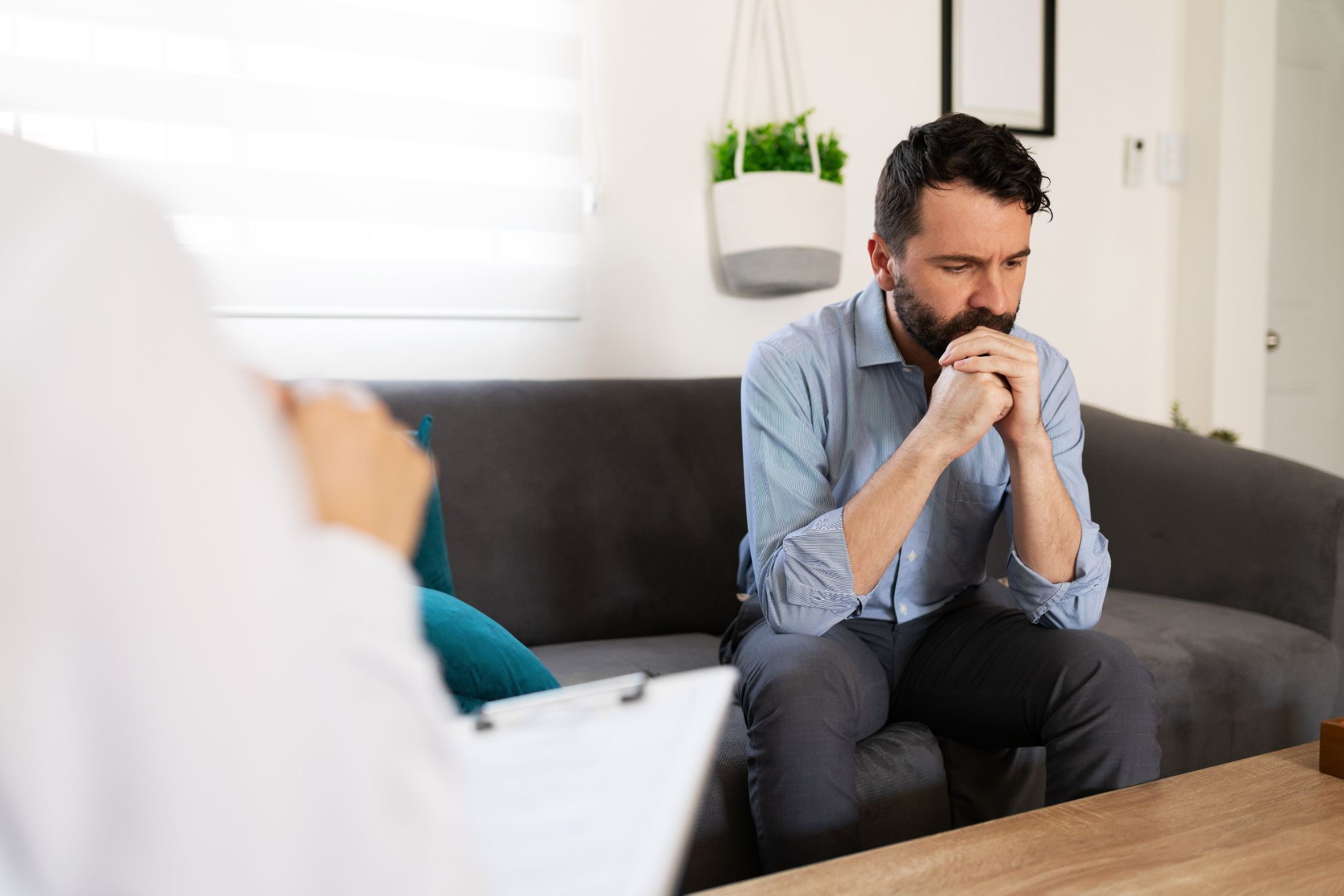 Hispanic man with depression and anxiety listening to the professional advice of his female psychiatrist