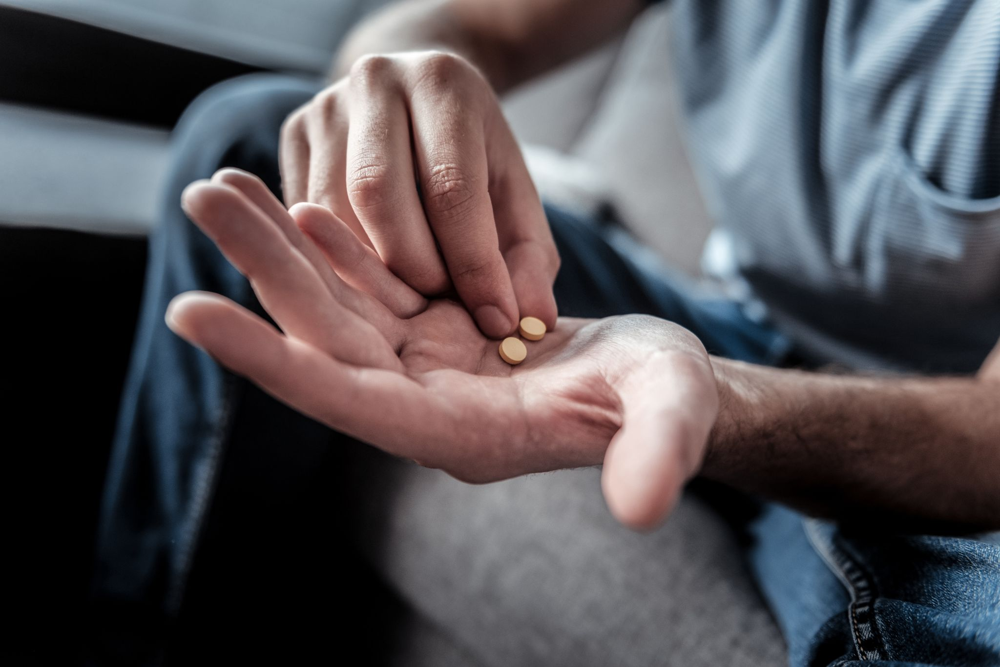 pills in hands of a man while suffering from depression