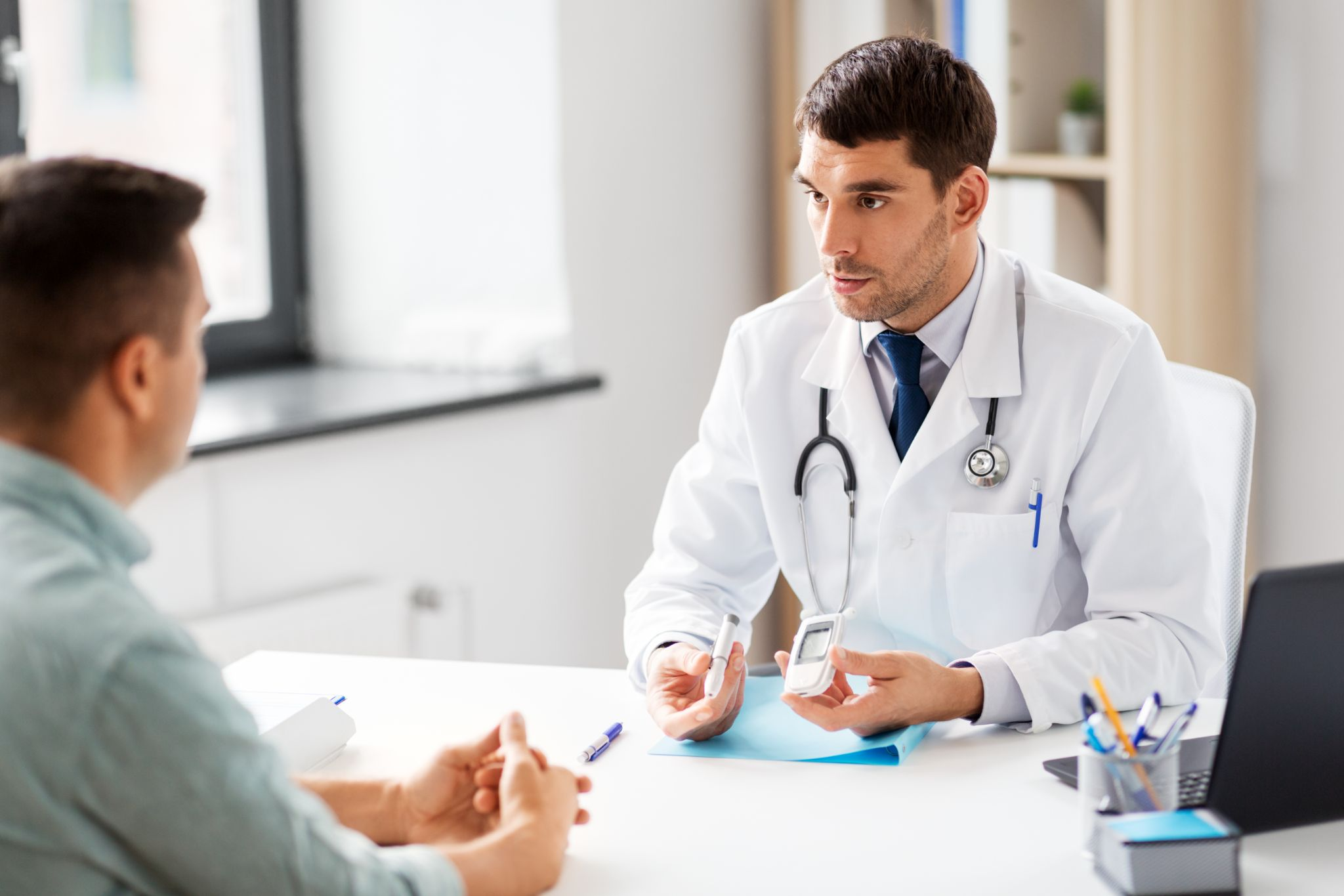 doctor with glucometer and insulin pen device talking to male patient