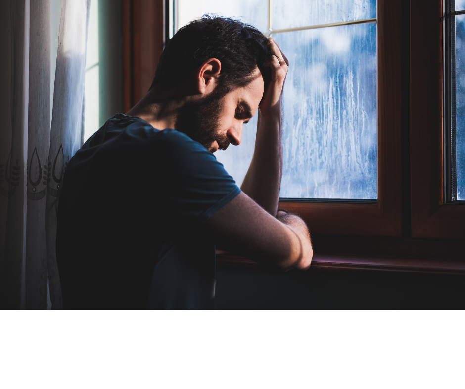Young sad man sitting by the window in regret