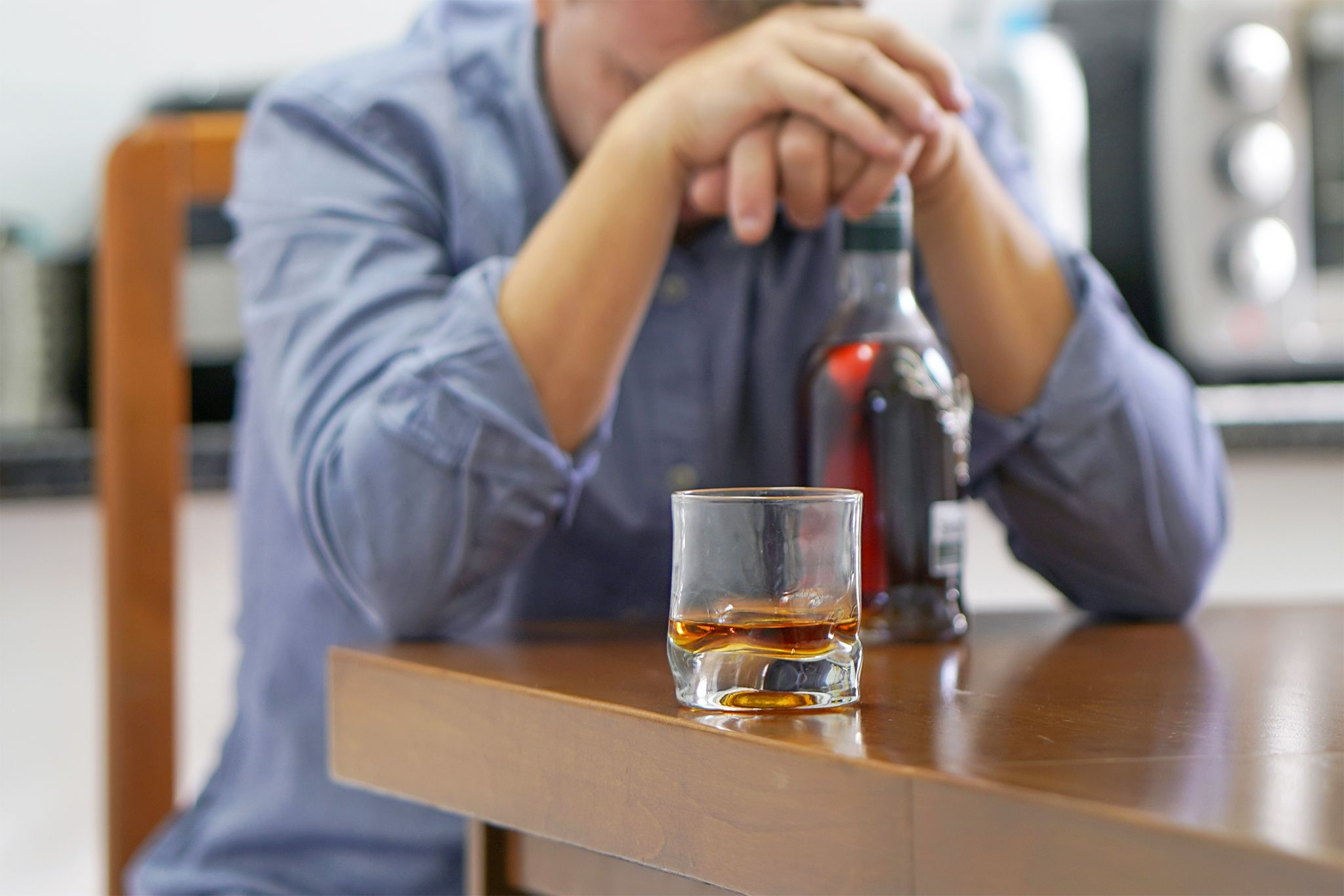 A depressed man with bottle of whiskey on the kitchen