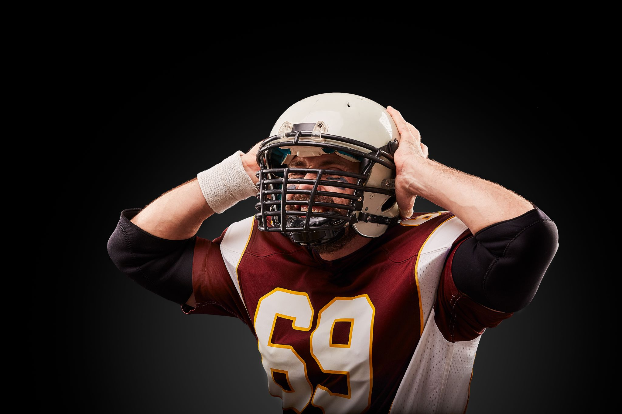 American football player in a helmet holding his head in pain