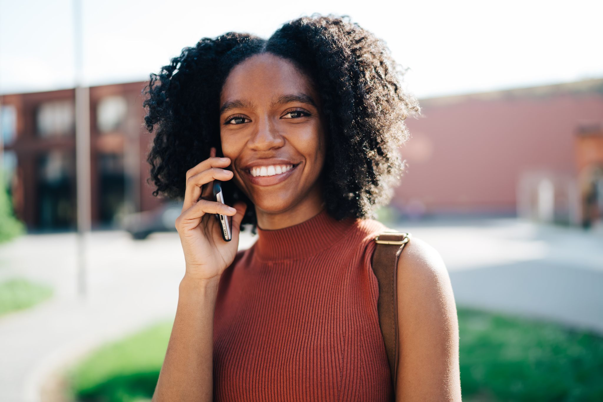 happy African American female student chatting on smartphone