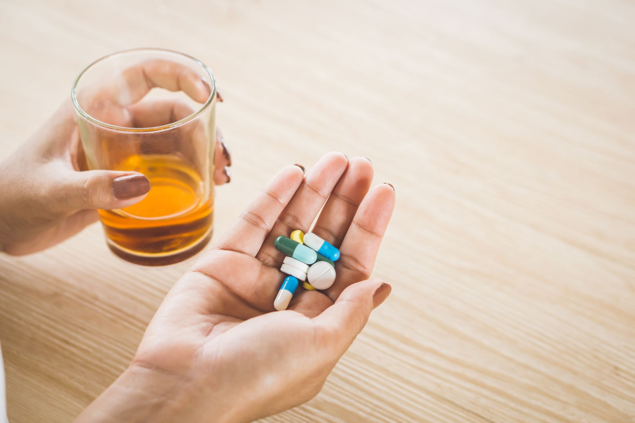 stress woman taking medicine with glass of alcohol