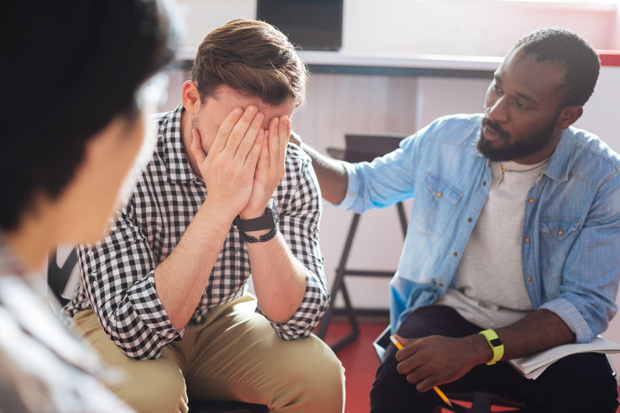 black man putting his hand on the shoulder of a crying person while talking to him