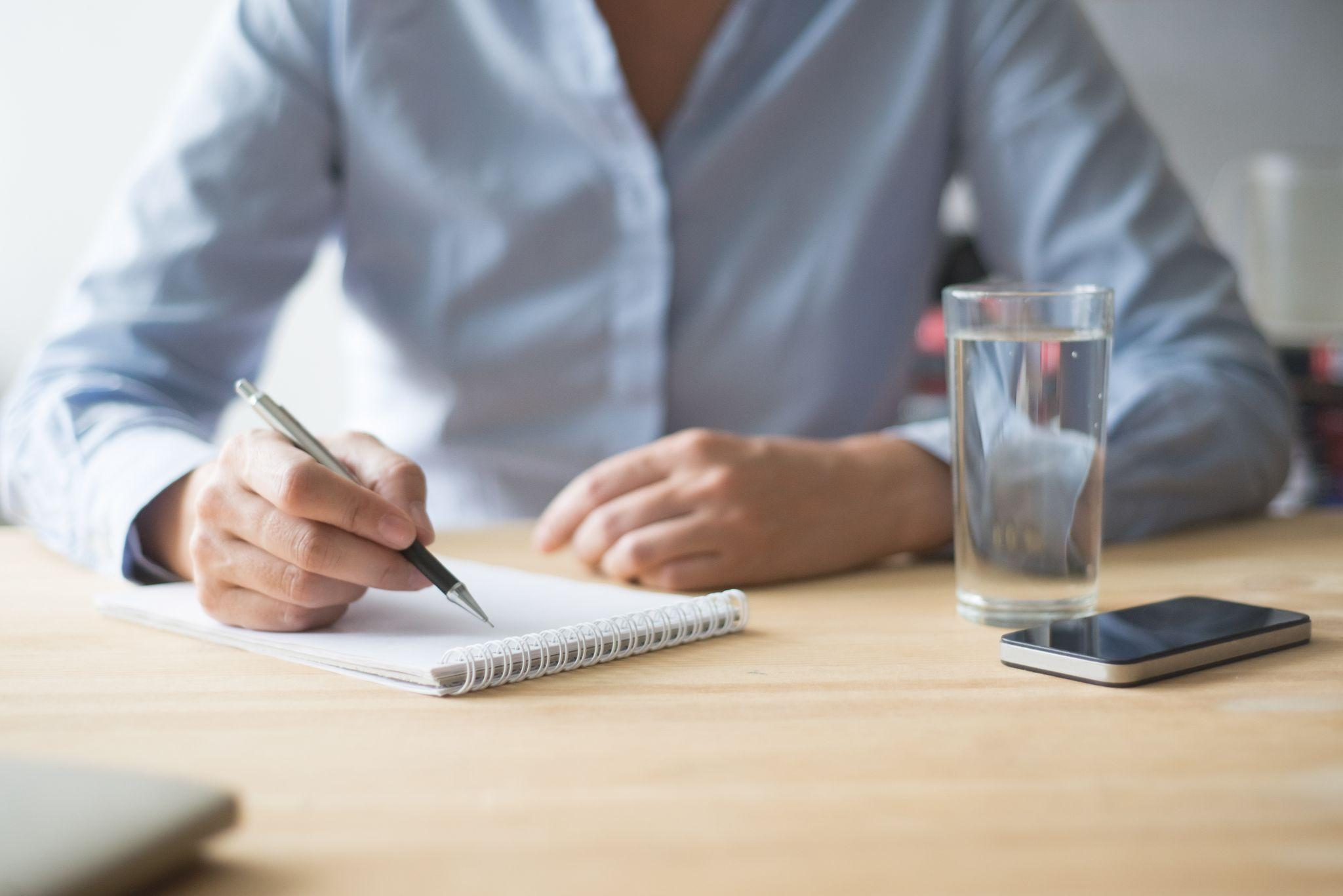 Woman Writing in Notebook in Office